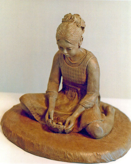 Photo of clay sculpture of a young girl holding a birds nest in her hands