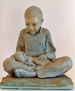 Photo of a sculpture of a young boy with a sleeping puppy in his lap
