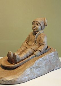 Photo of a sculpture of young child sledding in the snow
