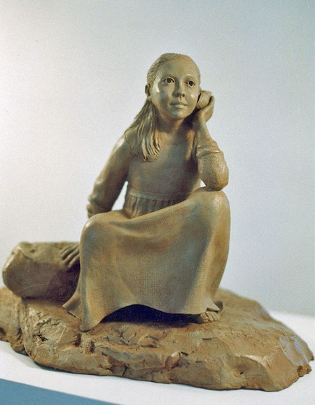 Photo of a sculpture of young girl listening to a sea shell