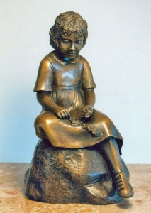 Photo of a sculpture of young girl stringing daisies