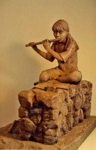 Photo of young girl playing flute while sitting on a wall