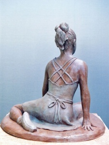 Photo of a sculpture of a young dancer sitting on the floor (back)