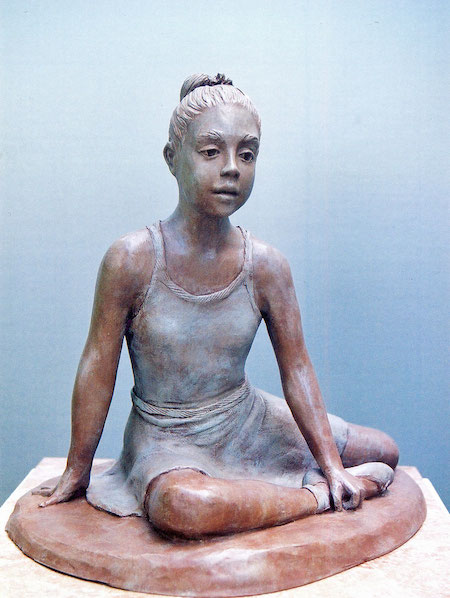 Photo of a sculpture of a young dancer sitting on the floor