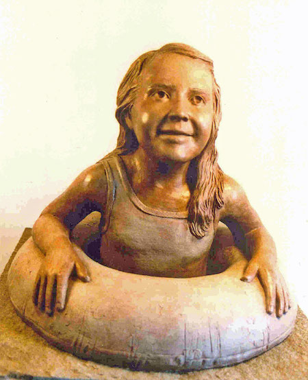 Photo of a sculpture of a young girl swimming with an inflatable tube