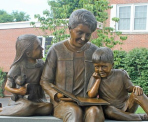Photo of a sculpture of a woman reading a book to two children
